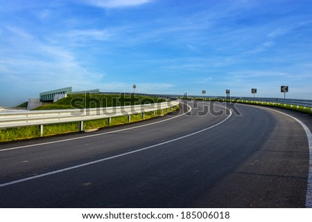 guard rail on country road over a blue sky - stock photo