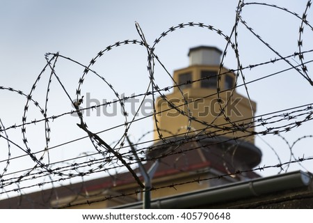 Guarding tower behind barbed wire fence stretched around prison walls - stock photo