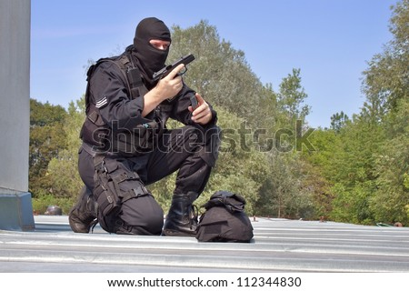 guarding VIPs, special forces policeman charges the gun on the roof - stock photo
