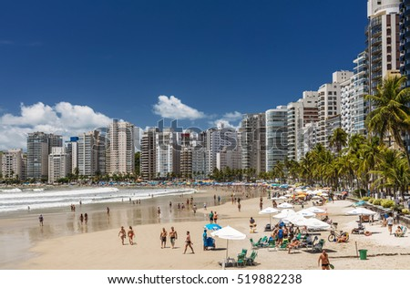 GUARUJA, BRAZIL - NOVEMBER 20: people relaxing on Pitangueiras beach with skyscrapers on the background in Guaruja, Sao Paulo, Brazil on November 20, 2016.