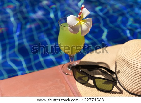 Guava green fresh juice smoothie drink cocktail, sunglasses and straw hat near swimming pool - Summer holiday concept