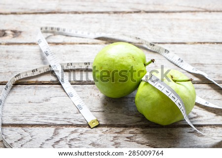 guava with measure tape for diet , on wooden, Healthy lifestyle concept - stock photo