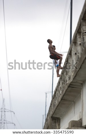 GUAYAQUIL, ECUADOR, FEBRUARY 19: Two unidentified teenagers jumping back side from a tall concrete bridge to the river in the city of Guayaquil. Ecuador 2015.