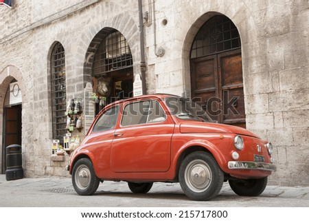 GUBBIO, ITALY - MAY 13; Iconic orange Fiat 500 parked in historic street on traditional buildings on May 13, 2011. The small retro Fiat 500 has become a symbol of Italian culture. - stock photo