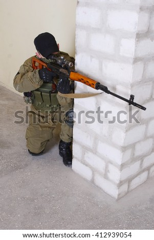 guerillas sniper with sniper rifle inside the building - stock photo