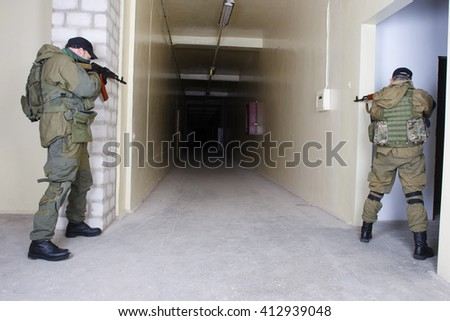 guerillas with AK-47 rifle inside the building - stock photo