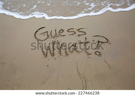 Guess what? A message written in the sand at the beach.  - stock photo