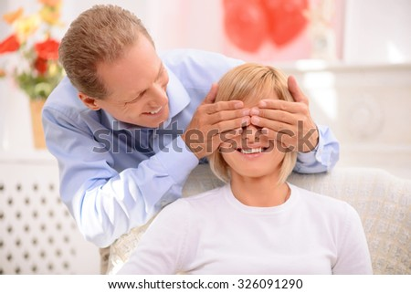 Guess who. Cheerful handsome agreeable man holding his hands on the face of his wife and closing her eyes while expressing gladness - stock photo
