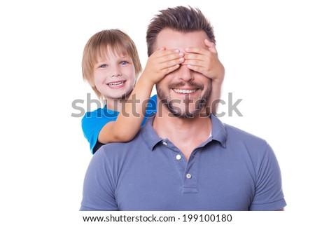 Guess who! Playful little boy covering his father eyes with hands and smiling while both standing isolated on white background - stock photo