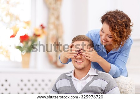 Guess who. Pleasant overjoyed cheerful young girl holding hand on the face of her boyfriend while closing eyes and expressing joy - stock photo