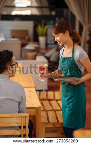 Guest being served a cocktail by an attractive waitress - stock photo