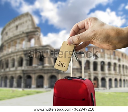 guest holding the hotel room key at Roma with Coliseum in the background - stock photo
