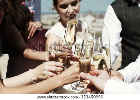 Guests at a wedding with the bride and groom clink glasses of champagne or white wine