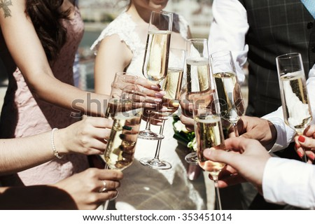 Guests at a wedding with the bride and groom clink glasses of champagne or white wine - stock photo