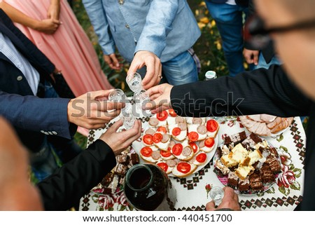Guests drink vodka standing under a table with appetizers - stock photo