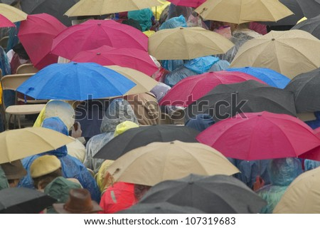 Guests hold umbrellas in the rain as they attend the official opening ceremony of the Clinton Presidential Library November 18, 2004 in Little Rock, AK