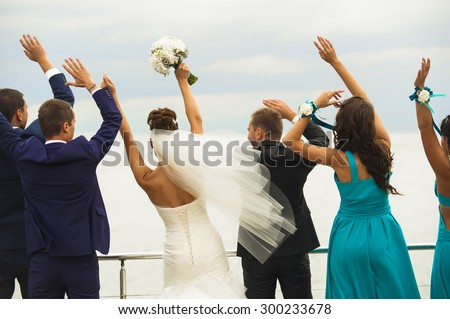 Guests on the wedding celebration are standing by the sealine, holding their hands up and playing the game. - stock photo