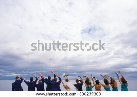 Guests on the wedding celebration are standing on the river pier, holding their hands up and looking in to the distance. - stock photo