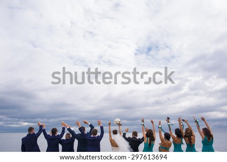 Guests on the wedding celebration are standing on the river quay, holding their hands up and looking in to the distance. - stock photo