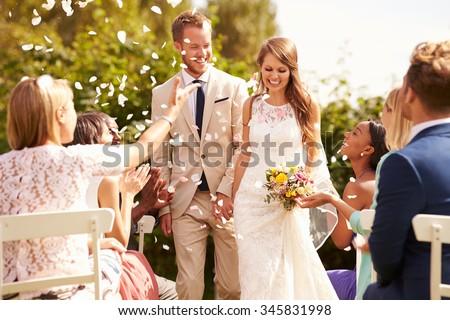 Guests Throwing Confetti Over Bride And Groom At Wedding - stock photo