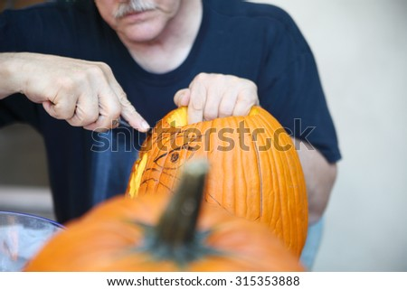 Guided by his sketch, an older man carves a jack o' lantern.  - stock photo