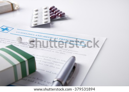Guidelines and medical prescription with drug blisters on a white glass table. Horizontal composition. Elevated view. - stock photo
