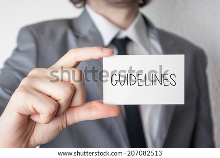 Guidelines. Businessman in suit with a black tie showing or holding business card