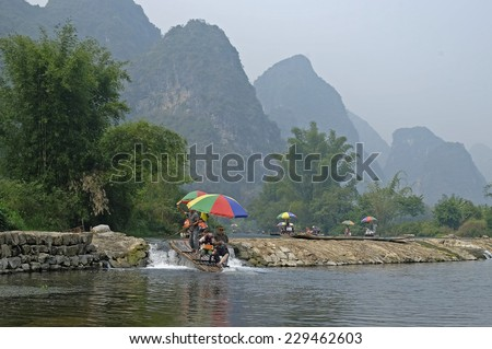 Guilin, China - 14 October 2014 - Tourists ride on a bamboo raft along the Yulong river, in Guilin China. Yangshuo County, in the northeast of Guangxi, China is one of the tourist spots in Guilin.