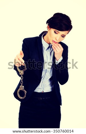 Guilty businesswoman holding metal handcuffs. - stock photo
