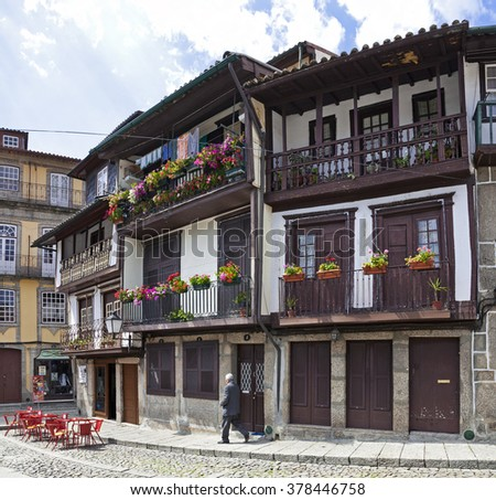 Guimaraes, Portugal - April, 2015: A local passes by the medieval buildings in the Santiago Square, also known as Sao Tiago or Sao Thiago, in the Historical Center. Unesco World Heritage Site. - stock photo