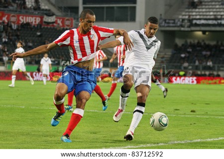 GUIMARAES, PORTUGAL - AUGUST 25: Joao Miranda(L) of At.Madrid(ESP) tries to win the ball from Abdelghani Faouzi,Vitoria SC(POR) at the 2011\12 UEFA Europa League on August 25, 2011 in Guimaraes, Portugal - stock photo