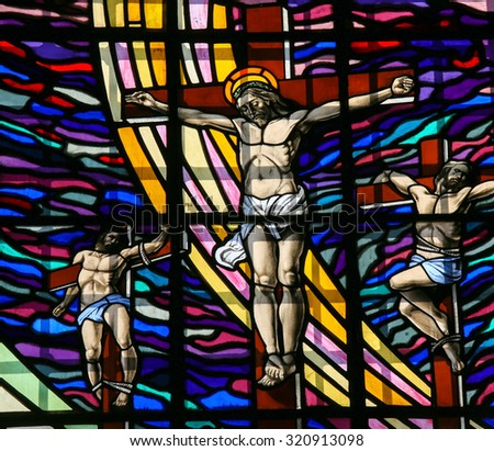GUIMARAES, PORTUGAL - AUGUST 7, 2014: Stained glass window depicting The Crucifixion of Jesus in the Santos Passos church in Guimaraes, Portugal. - stock photo