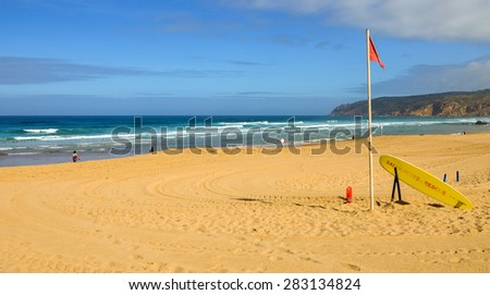 GUINCHO BEACH, PORTUGAL MAY 8, 2015: Red flag on the Guincho beach in Portugal. Windy weather, some waves people walking, some sitting on the beach. Golden sand. Popular kitesurfung and surfing spot.