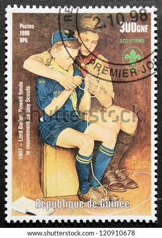 GUINEA - CIRCA 1998. A postage stamp printed by GUINEA shows two Boy Scouts, circa 1998. - stock photo