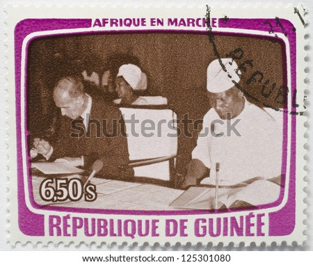 GUINEA - CIRCA 1979: A stamp from Guinea shows image of a foreign dignitary and local host sitting down signing some documents, from the Africa in Motion series, circa 1979