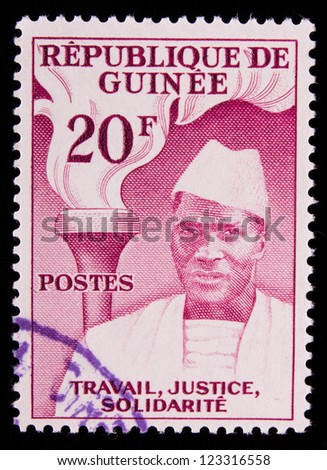 GUINEA - CIRCA 1959: A stamp printed in Guinea shows a black man in white clothes and a fire behind him , circa 1959.