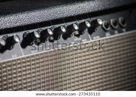 guitar amplifier in low-key,soft focus of knobs and def of field effect - stock photo