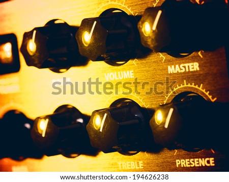 guitar amplifier panel in yellow light, closeup - stock photo