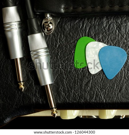 guitar amplifier with cable jack and plectrums, closeup - stock photo