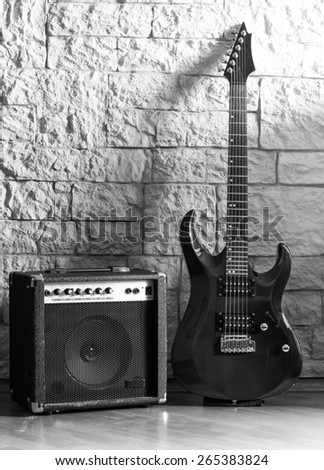 Guitar and amplifier on a stone background - stock photo
