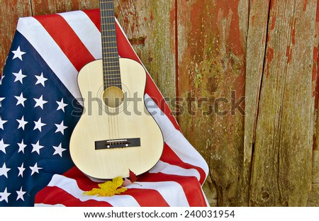 guitar and autumn leaves on an American flag by old weathered barn - stock photo