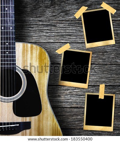Guitar and old photo frame on wood background. - stock photo