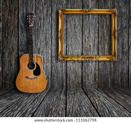 guitar and picture frame in vintage wood room