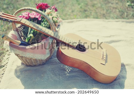 Guitar, basket with wine and bouquet of flowers. Vintage tender background. Romance, love, date, Valentine's day - concept - stock photo