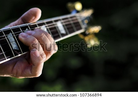 guitar chord played outdoors in a green park with trees as background - stock photo