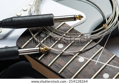 Guitar frets with strings, cable and jacks - stock photo