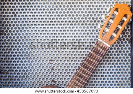 Guitar leaning on the metal grid background, copy space. - stock photo