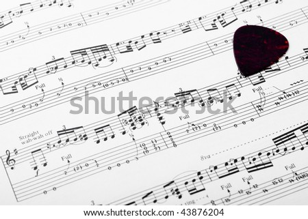 Guitar music sheet with pick