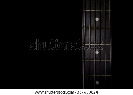guitar neck isolated on black background, horizontal view, low key image
