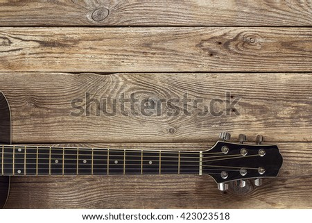 Guitar neck on the background of old grunge boards. Place for text. Top view - stock photo